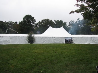 a long white tent with a tall part in the middle