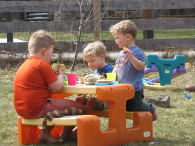 the boys sharing a picnic at the plastic table