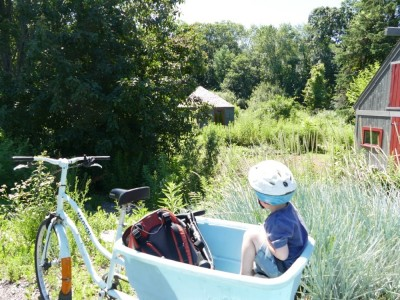 Lijah in the cargo bike looking at a wildflower garden and farmy shed