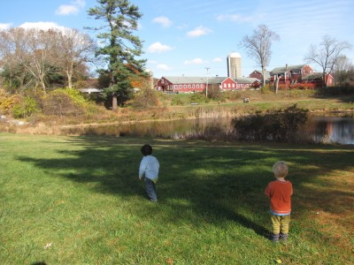 Zion and a friend on a lawn with pond and farm behind them