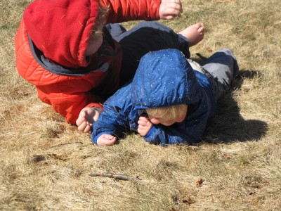 Harvey and Zion wrestling in the grass, bare-footed and winter-coated