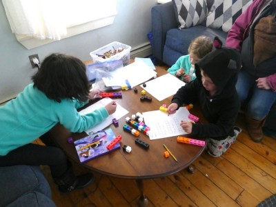 Lijah and two friends doing math work in our living room