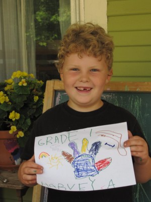 Harvey on the front porch, smiling and holding his Grade 1 sign
