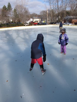 Harvey drooping on his skates on the outdoor rink, Nisia watching