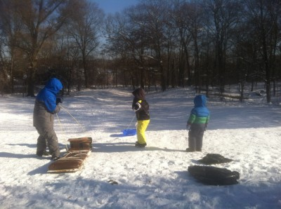 the boys at the top of a sledding hill