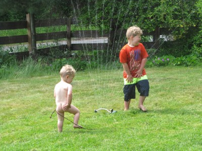 Harvey and Lijah playing in the sprinkler on the lawn
