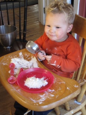 Lijah in the high chair making a mess with flour