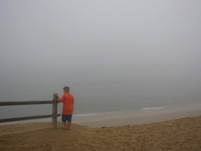 Harvey standing atop a dune bluff over the foggy atlantic