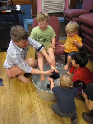 me washing Harvey's feet at church, with other kids looking on