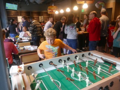 Harvey playing foozball at a crowded party