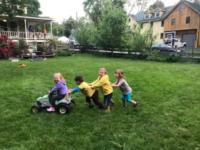 Lijah and two friends pushing a third on our toy tractor
