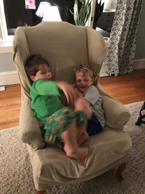 Lijah and Liam sleepily fooling around in an arm chair