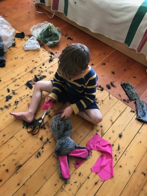 Lijah sitting on the bedroom floor with a half-made stuffed bunny, surrounded by fur debris