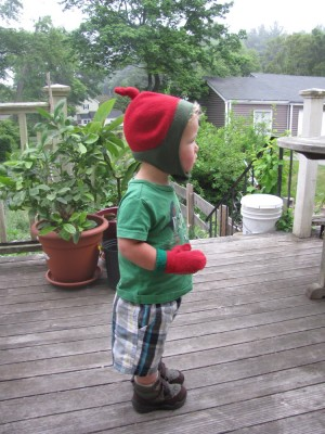 Lijah on the back porch wearing hat and mittens