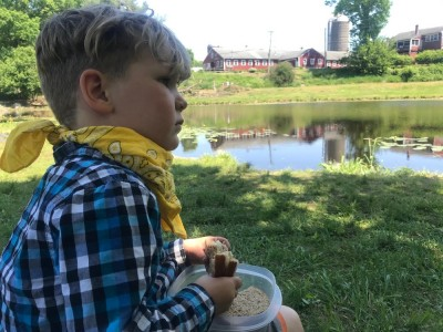 Lijah eating a sandwich by the pond at Great Brook