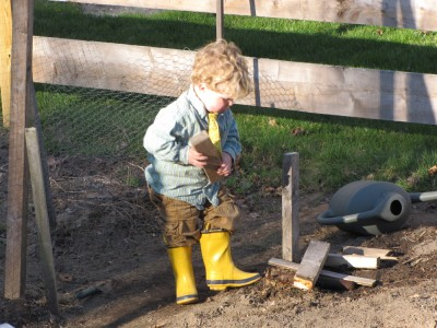 Harvey playing in the garden wearing yellow rain boots and a yellow tie