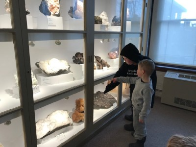 Harvey and Zion looking at minerals in a museum cabinet