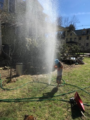 Lijah playing in the spray from a hole in the hose