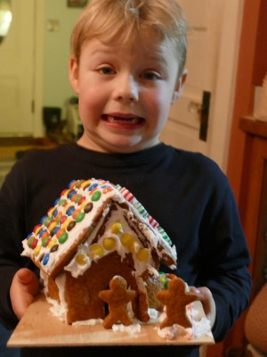 Zion holding his gingerbread house