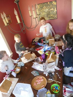 busy around the table with candy, frosting, and gingerbread