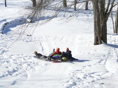 the bigger kids sledding down a hill in a bunch