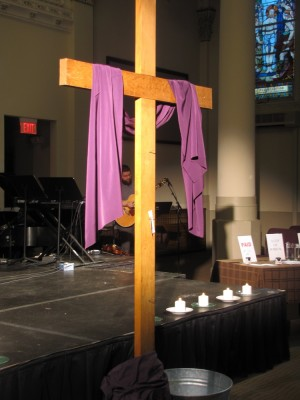 the wooden cross at the front of the church, draped with purple