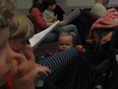 Lijah peeking over Mama's leg during the service