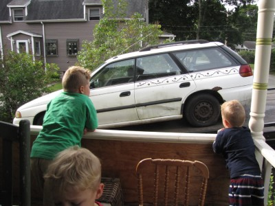 the boys watching the white car get towed away