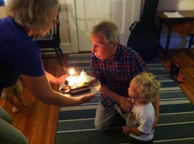Grandpa David blowing out his birthday candles, Lijah by his side