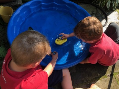 Zion and Lijah playing with boats in a wading pool