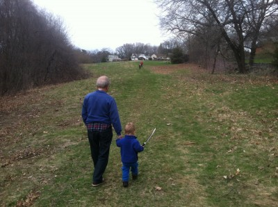 Lijah with his sword walking with grandpa in a field, the other boys up ahead