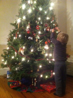 Zion reaching up to put an ornament on a Christmas tree