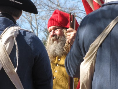 a bearded reenactor in a red cap