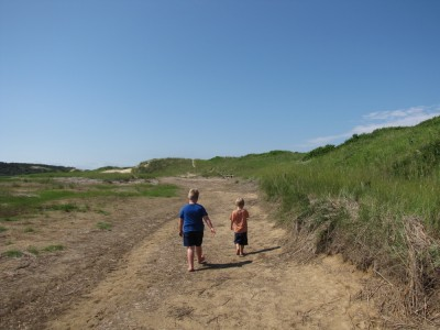 Harvey and Zion walking on a path by a dune