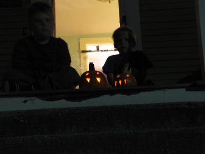 Zion and Harvey sitting on the dark porch with their jack-o-lanterns
