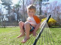 Lijah sitting up on the end of the hammock
