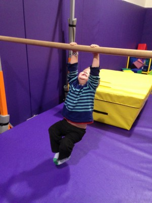 Lijah swinging from a bar at the playspace gym