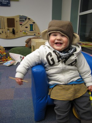 Lijah in the kids room at the library, in monkey hat