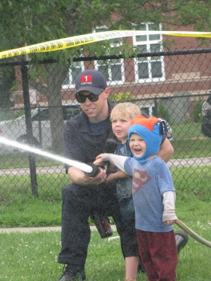 Zion spraying the firehose, with Lijah's assistance