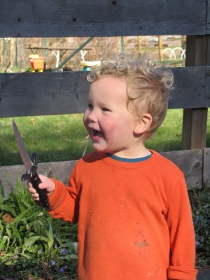 Lijah laughing by the fence, holding his little sword