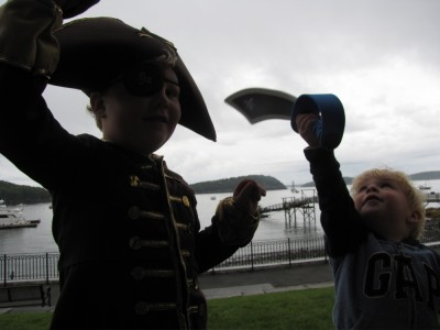 Harvey in full pirate gear and Zion with a sword, with the harbor behind them