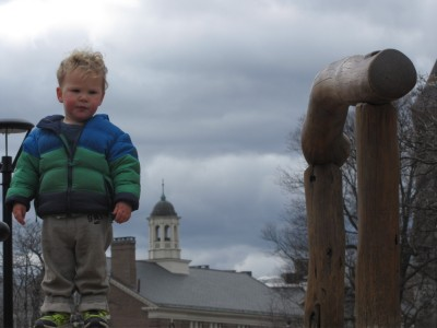 Lijah atop a playground hill with a university tower in the background