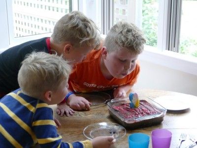 Harvey and brothers blowing out a birthday candle
