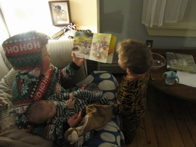 Harvey holding a baby, reading to Lijah; all in PJs