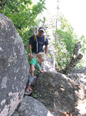 Harvey hiking among boulders with Dada following
