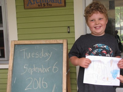 Harvey smiling holding his second grade sign