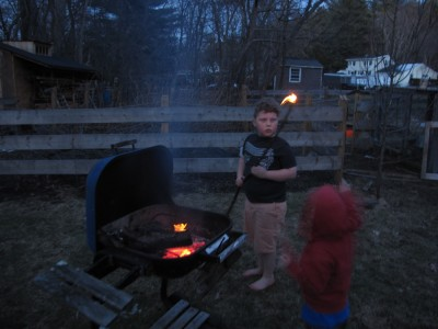 Harvey and Zion playing with fire, Harvey holding a burning stick