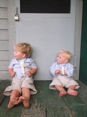 Zion and Harvey sitting against a cabin door wearing matching outfits