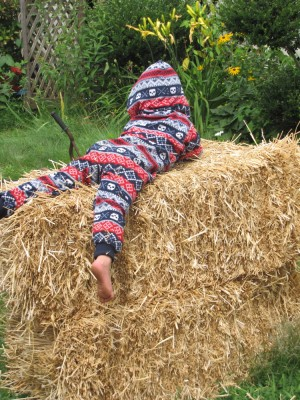 Lijah lying on hay bales in his (Zion's actually) pajamas