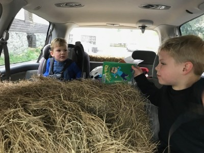 Zion and Lijah in the car looking over hay bales